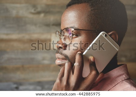Profile portrait of attractive black man wearing spectacles looking through the window while listening to messages on his mobile phone, with thoughtful and calm face expression against wooden wall - stock photo
