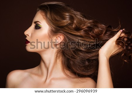 Profile portrait of beautiful brunette girl is holding her healthy curly long hair by hands - stock photo