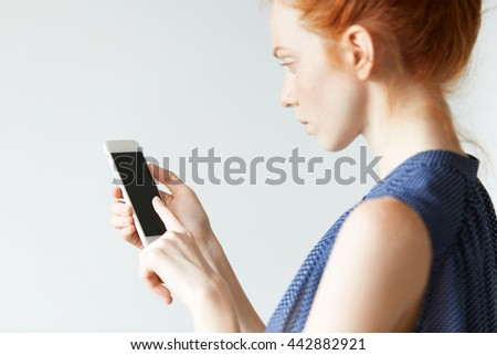 Profile portrait of beautiful ginger female in dot dress using touch screen smart phone with copy space for your text or promotional content, browsing the Internet. Selective focus on the phone - stock photo