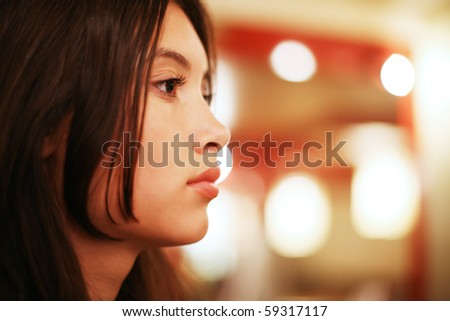 Profile portrait of beautiful young Asian woman indoors. Shallow DOF. - stock photo