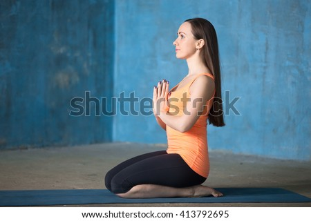 Profile portrait of beautiful young woman dressed in bright sportswear enjoying yoga indoors. Yogi girl working out in grunge interior with blue wall. Meditating or breathing in vajrasana. Full length - stock photo