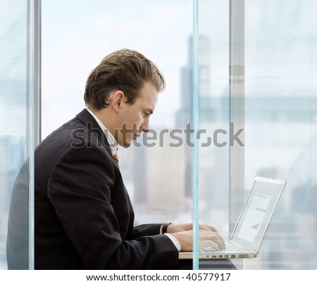 Profile portrait of businessman sitting in front of office windows, using laptop computer.