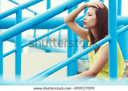 Profile portrait of gorgeous young woman wearing yellow-green handmade knitted top and posing between blue metal constructions. Urban style. Close up. Copy-space. Outdoor shot