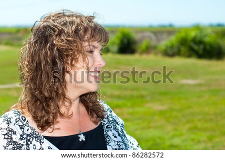Profile portrait of happy, smiling content middle-aged woman in park setting in image with copy space - stock photo