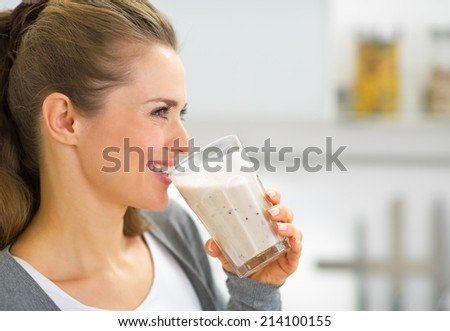 Profile portrait of happy young woman drinking fresh smoothie - stock photo