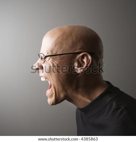 Profile portrait of mid-adult Caucasian male screaming. - stock photo