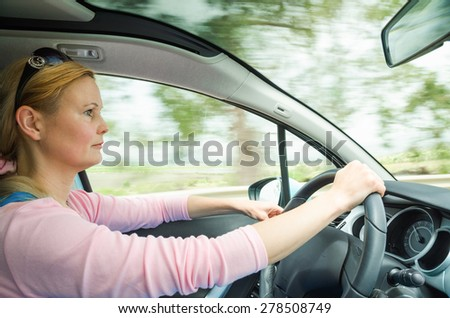 Profile portrait of serious calm woman careful and safe driving car on country road. Stock photo captured in active dynamic motion on high speed with slow shutter and blurred background. - stock photo