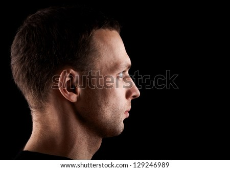 Profile portrait of serious young Caucasian man isolated on black background