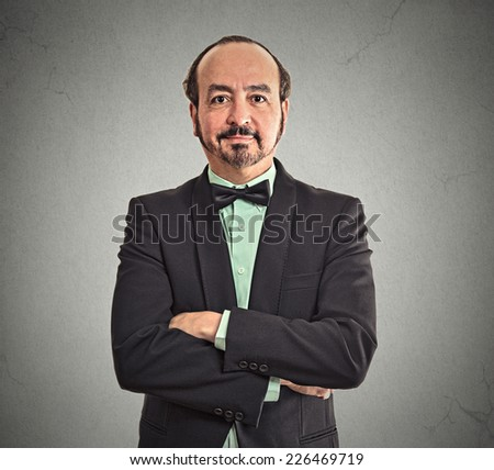 Profile portrait of smiling confident mature middle aged balding businessman wearing suit and bow tie with arms crossed isolated on gray wall office background. Positive face expression emotion - stock photo