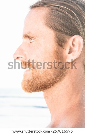 Profile portrait of the face of an attractive bearded man staring straight ahead with a quiet smile, close up view over a beach background with bright sunlight - stock photo
