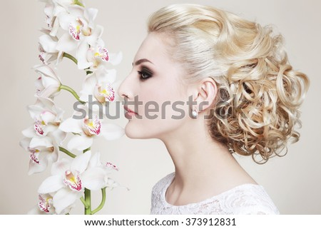 Profile portrait of young beautiful blonde bride with stylish prom hairdo