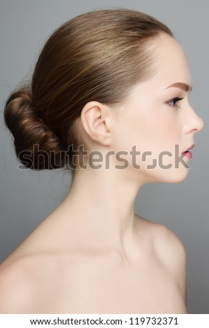 Profile portrait of young beautiful girl with hair bun - stock photo