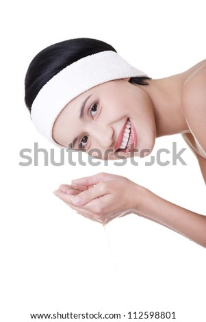 Profile portrait of young woman washing her face with clean water