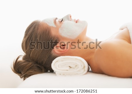 Profile portrait of young woman with revitalising mask on face laying on massage table - stock photo
