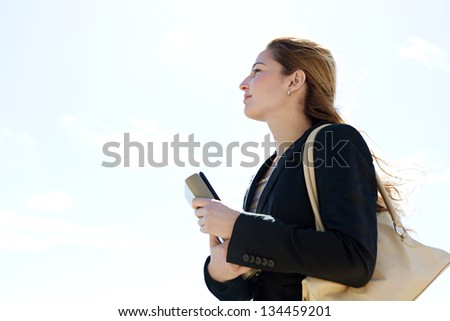 Profile portrait view of a young successful businesswoman carrying work folders and wearing a black suit, looking ahead against a blue sky background. - stock photo