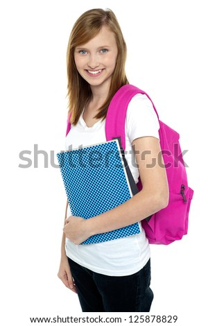 Profile shot of a beautiful young college student holding notebook and carrying pink backpack.