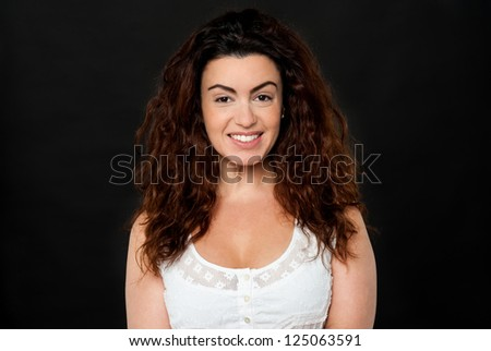 Profile shot of a gorgeous woman with lustrous hair on black background. - stock photo