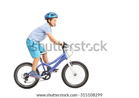 Profile shot of a little boy with blue helmet riding a small blue bike isolated on white background - stock photo