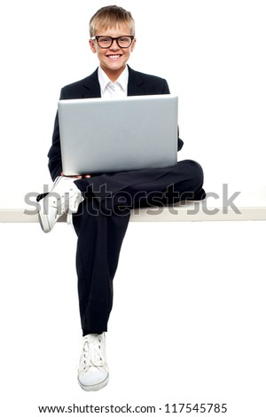 Profile shot of a smartly dressed young kid sitting with his legs crossed legs and working on a laptop - stock photo
