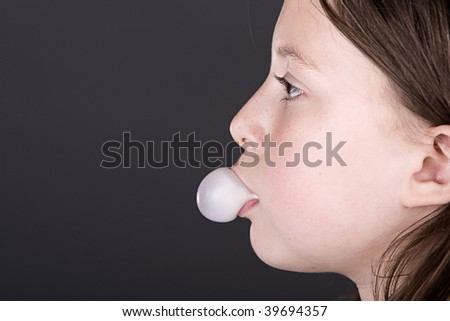 Profile Shot of a Young Child Blowing a Bubble with Gum - stock photo