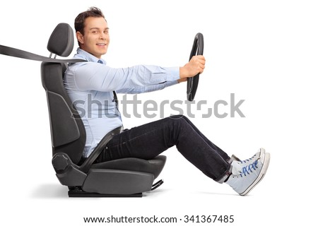 Profile shot of a young man driving seated on car seat and looking at the camera isolated on white background  - stock photo