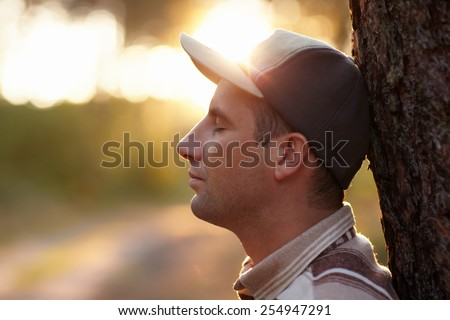 Profile shot of a young man with his eyes closed meditatively in an early morning forest - stock photo