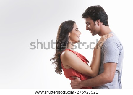 Profile shot of affectionate young couple looking at each other against white background - stock photo