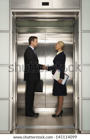 Profile shot of businessman and businesswoman shaking hands in elevator - stock photo