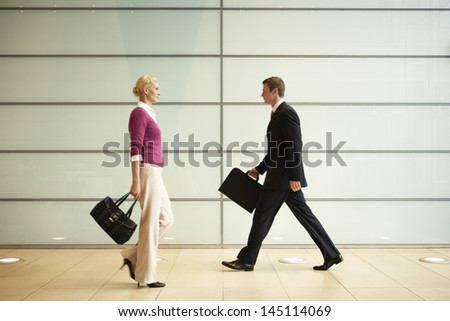 Profile shot of businesspeople with handbags walking in office corridor