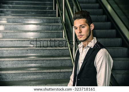 Profile shot of handsome young man inside train station looking at camera