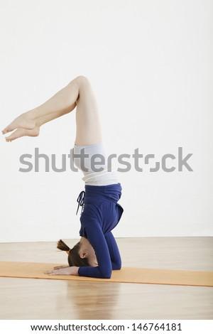 Profile shot of woman balancing on head at gym - stock photo