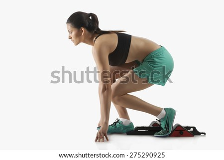 Profile shot of young female runner at starting block isolated over white background - stock photo