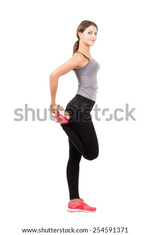 Profile side view of young sporty female beauty stretching leg.  Full body length portrait isolated over white background. - stock photo