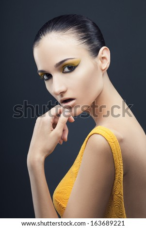 Profile sot of a young woman in a yellow dress - stock photo