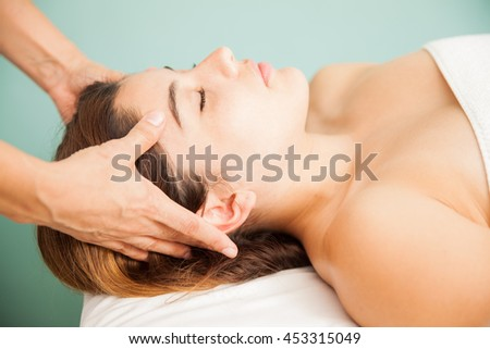 Profile view of a beautiful young woman getting a head massage by a therapist at a beauty clinic and spa