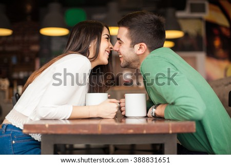 Profile view of a cute young couple reaching across the table and about to kiss - stock photo