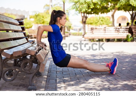 Profile view of a female athlete doing some tricep dips on a park bench - stock photo