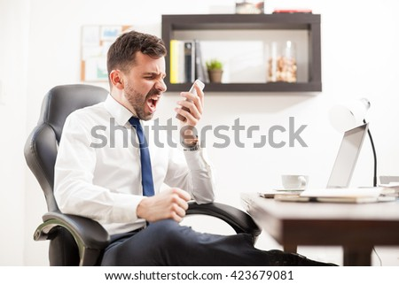 Profile view of a furious businessman yelling to a phone while seating in front of his desk in an office - stock photo