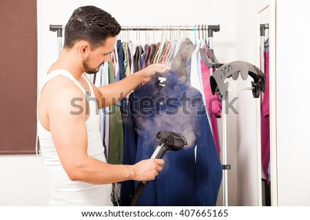 Profile view of a good looking young man using a steamer on a shirt before getting dressed - stock photo