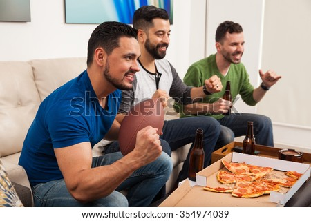 Profile view of a group of male friends cheering for their football team while watching the game at home - stock photo