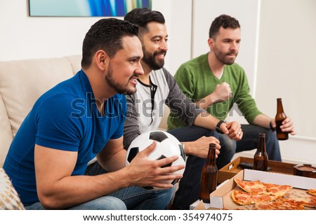 Profile view of a group of three male friends watching a soccer game on TV while drinking beer and eating pizza - stock photo