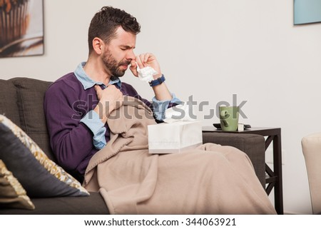 Profile view of a guy covered in a blanket feeling unwell and fighting a cold at home - stock photo