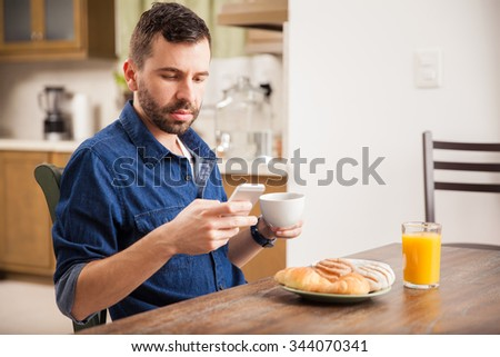 Profile view of a guy with a beard using his smartphone while having some breakfast at home - stock photo