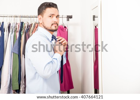 Profile view of a handsome young Latin man getting ready for work and putting on a tie in a dressing room - stock photo
