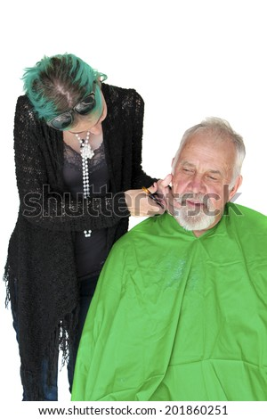 Profile view of a man about to get a shave from a female barber at a barber shop. isolated on white with room for your text - stock photo