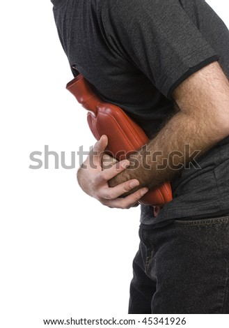 Profile view of a man holding a hot water bottle to soothe his stomach - stock photo