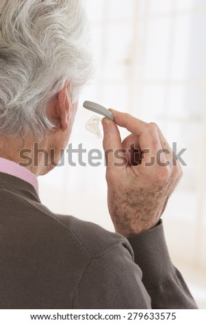 profile view of a senior woman inserting a hearing aid in his hear - stock photo