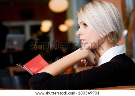 Profile view of a serious thoughtful young woman with trendy short blond hair sitting in a cafeteria - stock photo