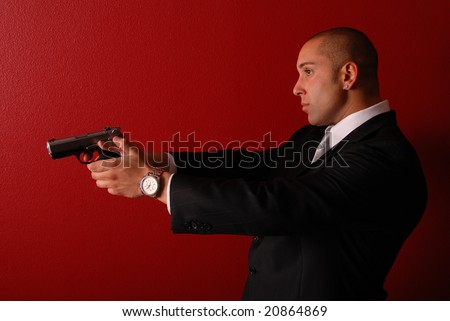 Profile view of a sexy man wearing a business suit holding a gun up in front of him. - stock photo