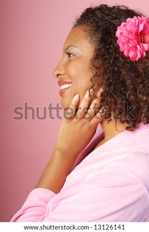 Profile view of a woman in a bathrobe at a spa on pink background - stock photo